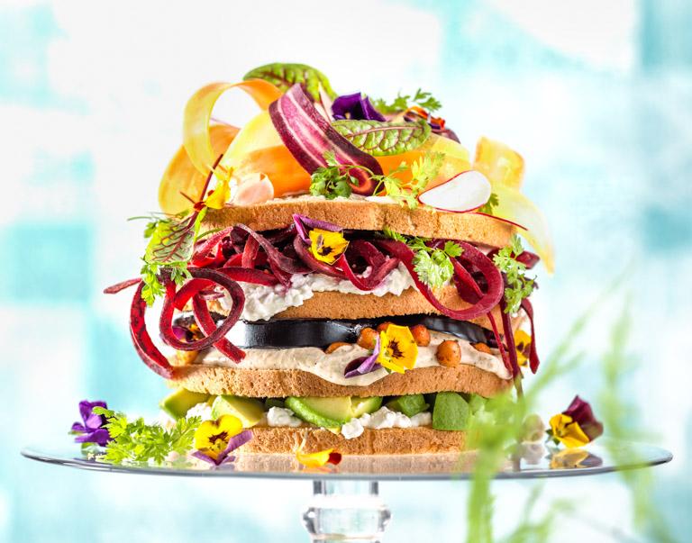 Een gezonde eyecatcher voor de lunch met veel verse groenten en diverse spreads. Samen snoepen van een groot brood dat net als een taart in puntjes wordt gesneden.