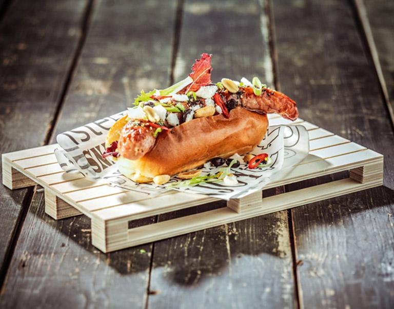 Hotdog gemaakt van kip met zoetzure saus, zwarte bonen, lente-ui, kroepoek, pinda's, slamix, rode peper en zwarte sesam.