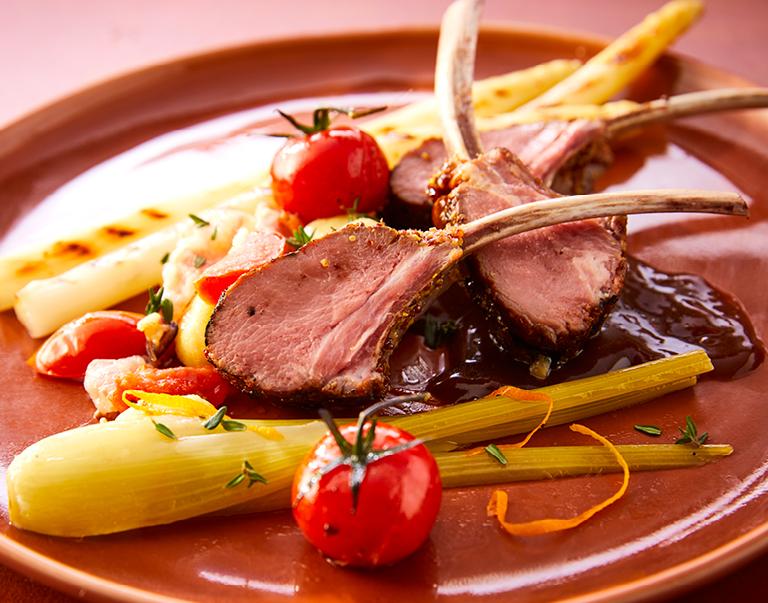 Geroosterde lamsrack met sous-vide gegaarde asperges, gnocchi, gepofte tomaat, gekonfijte venkel en saus van rode wijn en salie.