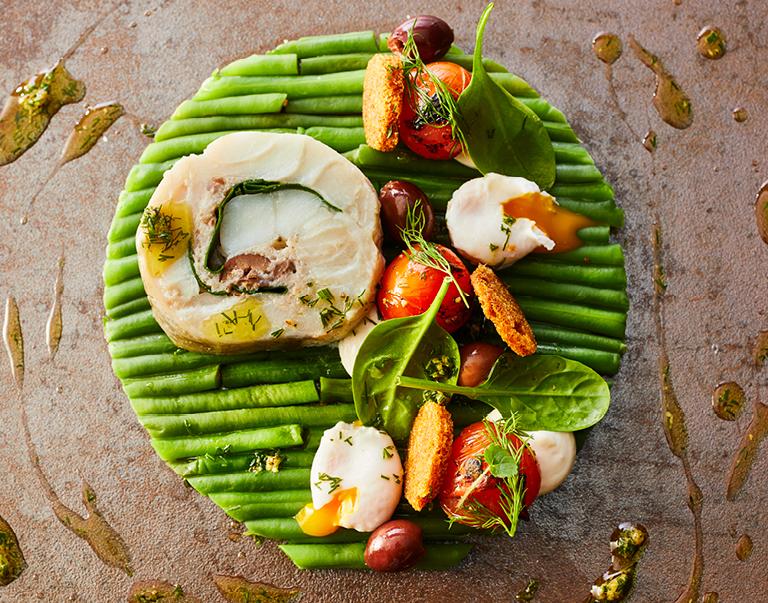Rouleau van kabeljauw, spinazie en olijven met een salade van groene boontjes, kwartelei, kerstomaatjes en gezouten citroen.