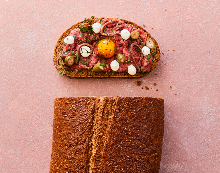 Rustiek brood belegd met steak tartare, kwartelei en gezouten ansjovis.