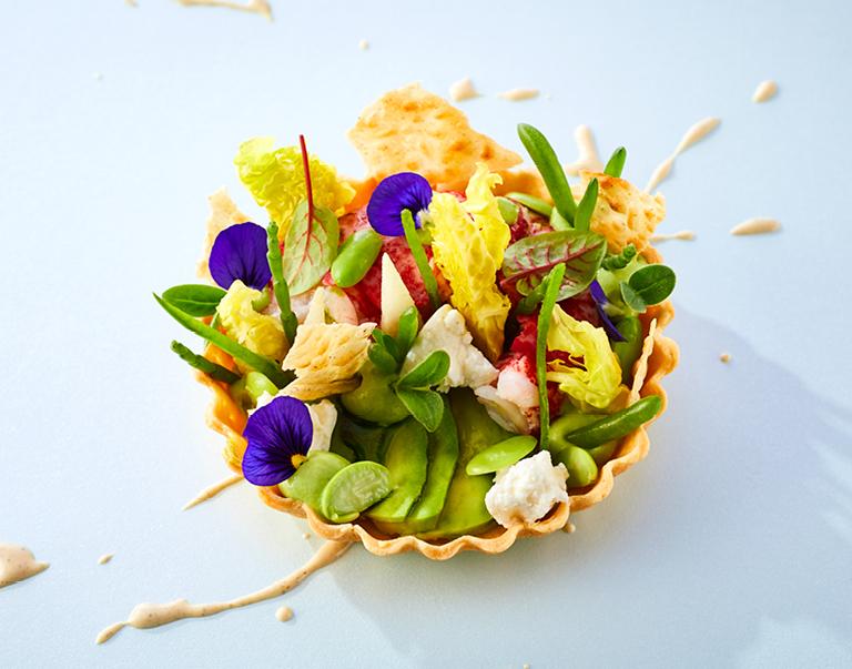 Tartelette van oosterscheldekreeft met een crème van doperwt, ricotta, zilte groenten, basilicum, ricotta en een jus van geroosterd hennepzaad.