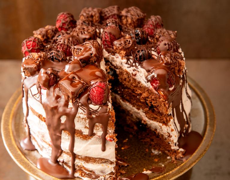 Een veganistische chocoladetaart met framboos en plantaardige slagroom.